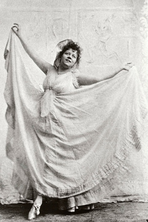 """This 1892 photograph shows Fuller costumed for her Serpentine Dance and holding a typical """"skirt dance"""" pose. While the connection with skirt dancing is evident, the image also reveals Fuller's innovations. She has done away with the skirt dancer's usual corseted bodice, moved the waistline higher, added more fabric to the skirt, and used sheer lightweight white silk (in lieu of a skirt dancer's pleated fabric) to serve as a mobile screen for her colored lights and projections. (Photograph by B.J. Falk. Jerome Robbins Dance Division, New York Public Library for the Performing Arts.)"""